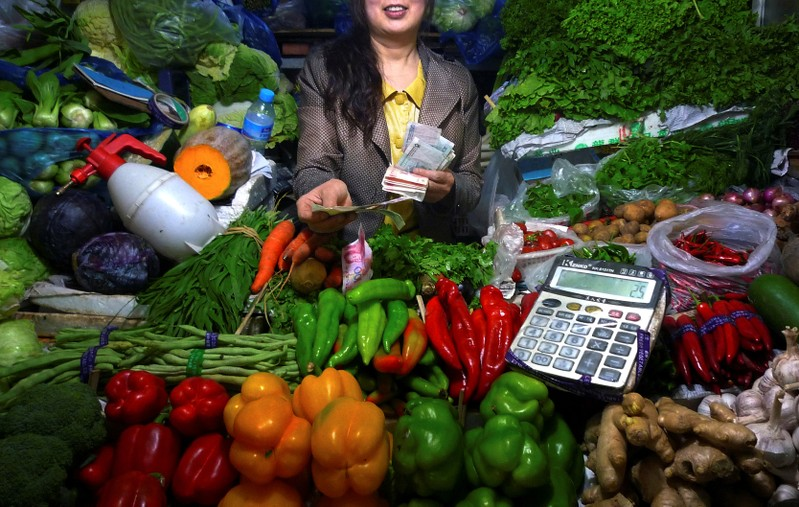 FILE PHOTO: A fruit and vegetable stall owner uses a calculator to work out prices for a customer at a small market in central Beijing