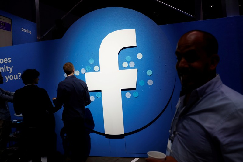 FILE PHOTO: Attendees walk past a Facebook logo during Facebook Inc's F8 developers conference in San Jose, California, United States