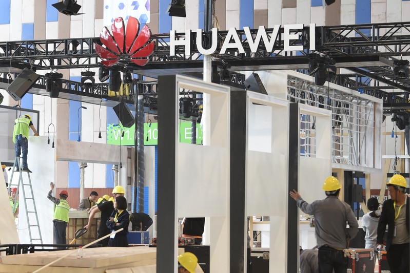Workers are seen near the booth of Huawei Technologies Co under construction at the venue of China International Big Data Industry Expo in Guiyang