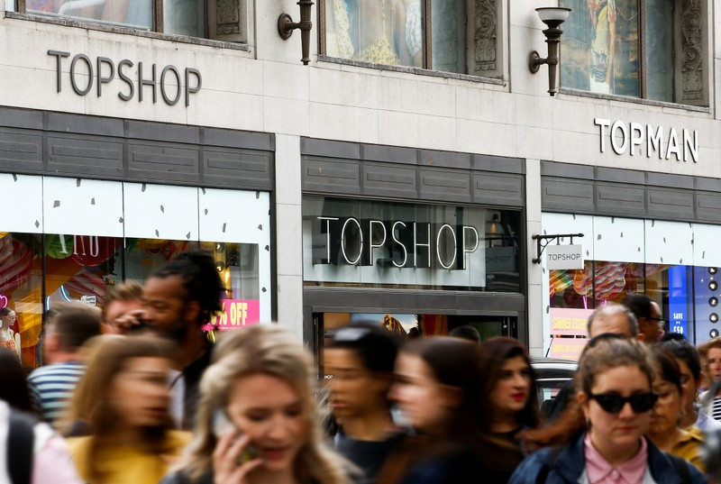 FILE PHOTO: People walk past a Topshop and Topman store, owned by Arcadia Group, in central London