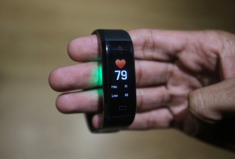 An employee displays the GOQii Vital activity tracker at their office in Mumbai