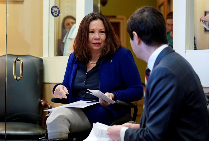 Senator Duckworth speaks with an aide before the announcement of the formation of the Senate Democrats' Special Committee on Climate Change in Washington