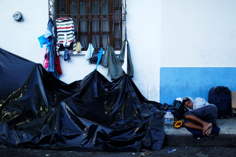 Central American migrants wait outside the Mexican Commission for Refugee Assistance (COMAR) in Tapachula