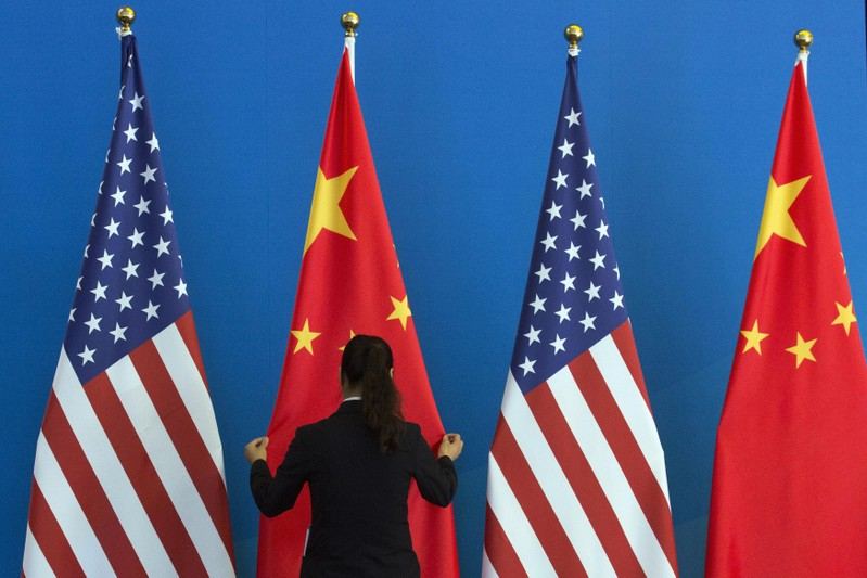 FILE PHOTO: A Chinese woman adjusts a Chinese national flag next to U.S. national flags before a Strategic Dialogue expanded meeting, part of the U.S.-China Strategic and Economic Dialogue (S&ED) in Beijing