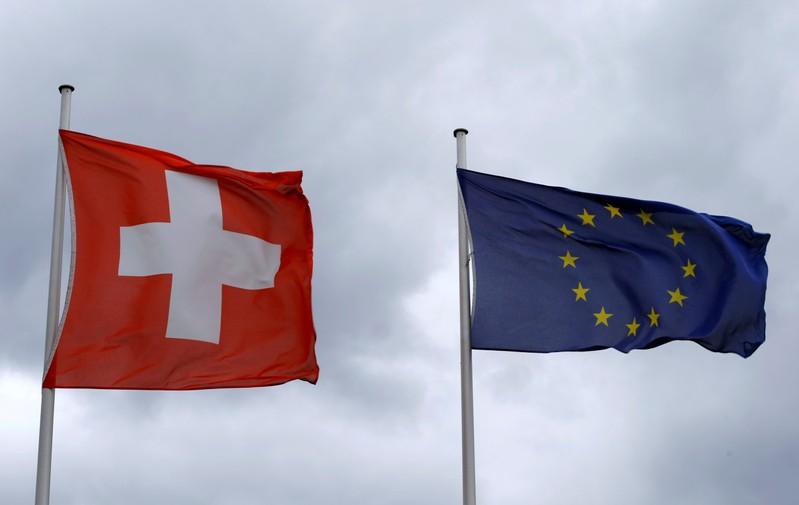 FILE PHOTO: An EU flag flies beside Switzerland's national flag near the German-Swiss border in Rheinfelden