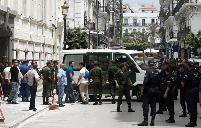 Police officers and members of national gendarmerie stand guard outside a court in Algiers