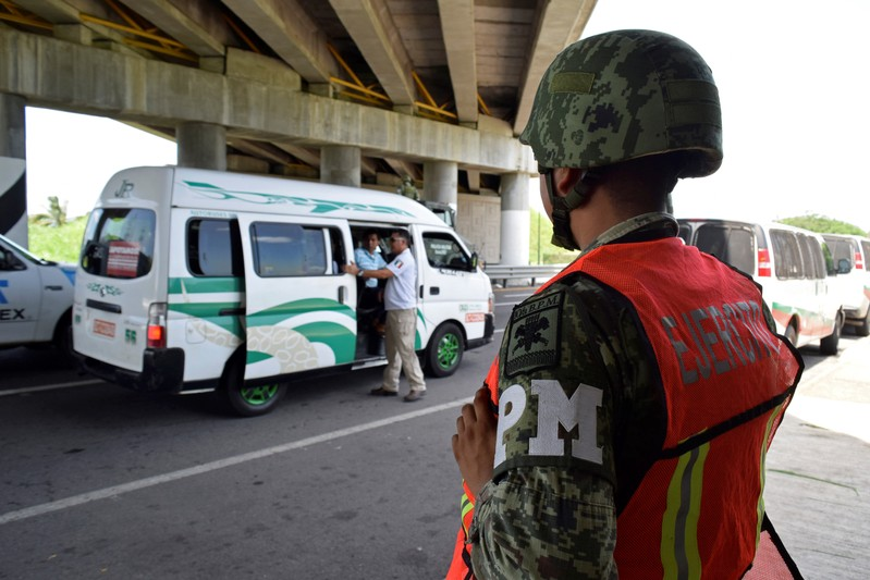 FILE PHOTO: A personnel of the National Migration Institute (INM) checks passenger's ID as a member of the Military Police keeps watch at a checkpoint on the outskirts of Tapachula