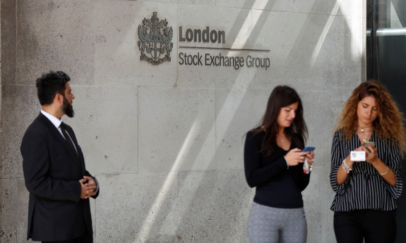 FILE PHOTO: People check their mobile phones as they stand outside the entrance of the London Stock Exchange in London