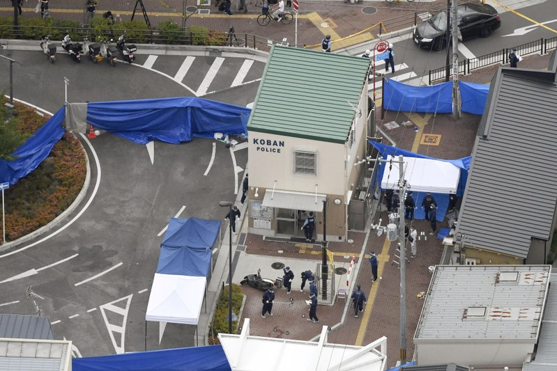 An aerial view shows police officers investigating the site where a police officer was found stabbed in front of a police box and the officer's gun, loaded with several bullets, was stolen, in Suita, Osaka