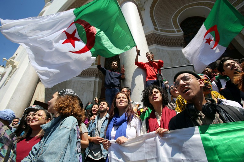 FILE PHOTO: Demonstrators hold flags during anti government protests in Algiers
