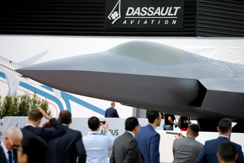 Visitors look at the French-German-Spanish New Generation Fighter (NGF) model during the 53rd International Paris Air Show at Le Bourget Airport near Paris