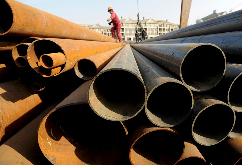 FILE PHOTO: A labourer walks on steel pipes at a steel market in Hefei