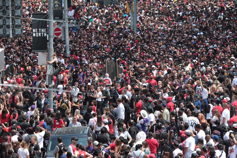 Toronto fans watch a man climb down a poll as they fill the streets in front of the city hall, during the Toronto Raptors NBA Championship celebration parade at Nathan Phillips Square in Toronto