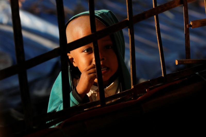 A Rohingya refugee child looks at others studying at a makeshift madrasa at the Burma Para refugee camp near Cox's Bazar