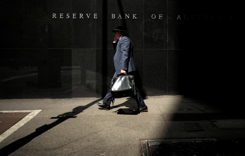 FILE PHOTO: A Sydney businessman walks into the light outside the Reserve Bank of Australia