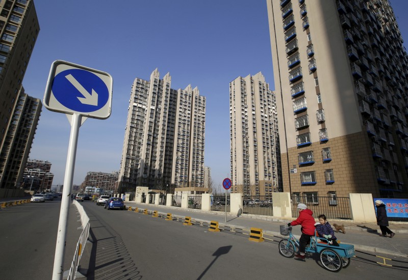 FILE PHOTO: A woman rides a tricycle carrying a child near a residential compound in Beijing's Tongzhou district