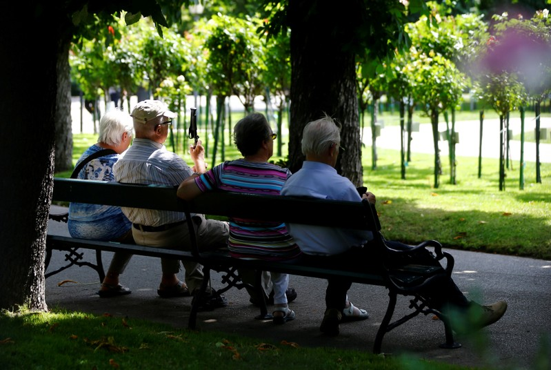 FILE PHOTO: A group of elderly people sit in the shade in a park in Vienna