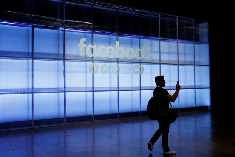FILE PHOTO: An attendee takes a photograph of a sign during Facebook Inc's F8 developers conference in San Jose
