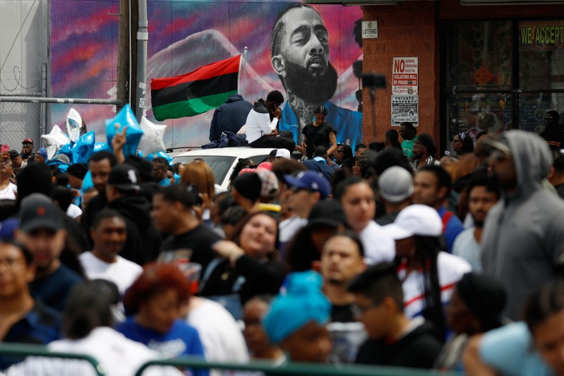 Fans wait for the funeral procession following a memorial for rapper Nipsey Hussle along Slauson Avenue in Los Angeles