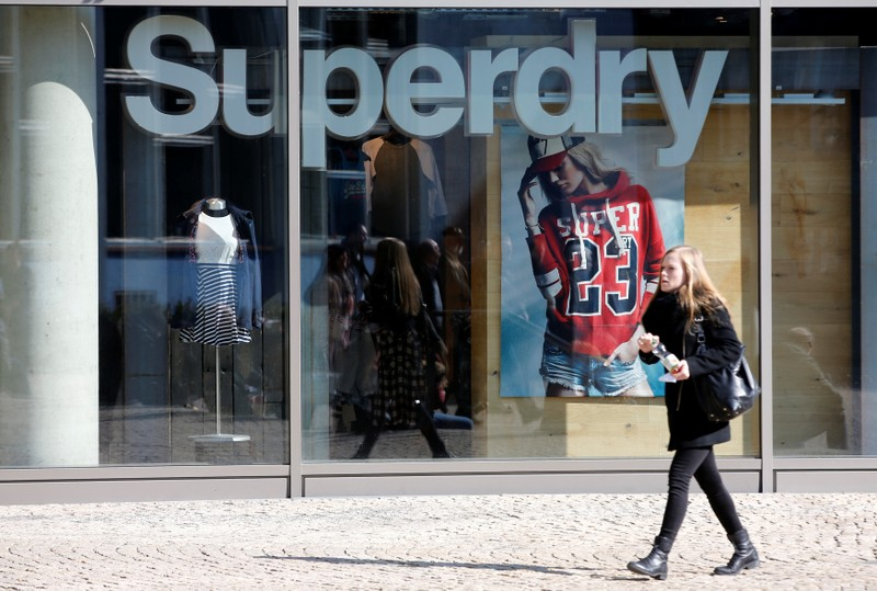 FILE PHOTO: A woman walks past a Superdry fashion store in Berlin