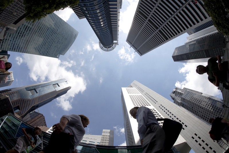 FILE PHOTO: People walking past office buildings at the central business district in Singapore