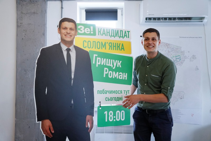 Roman Hryshchuk shows a banner with a life-size cutout of himself at his election headquarters in Kiev