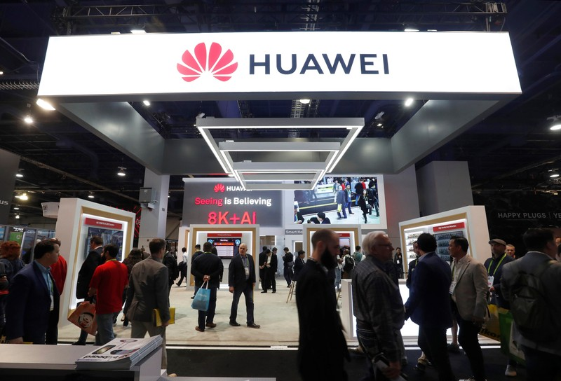 Participants pass by a Huawei booth at CES 2019 in Las Vegas.