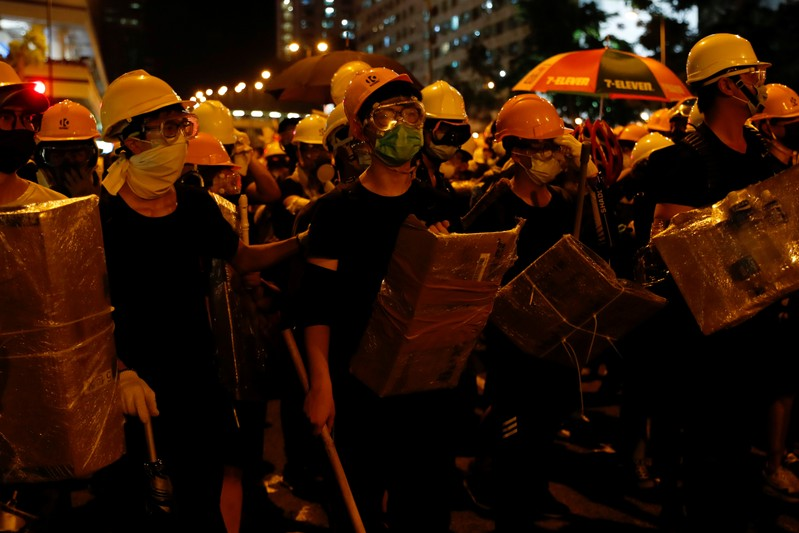 Anti-extradition bill protesters hold shields made from cardboard as they face riot police after a march at Sha Tin District of East New Territories, Hong Kong