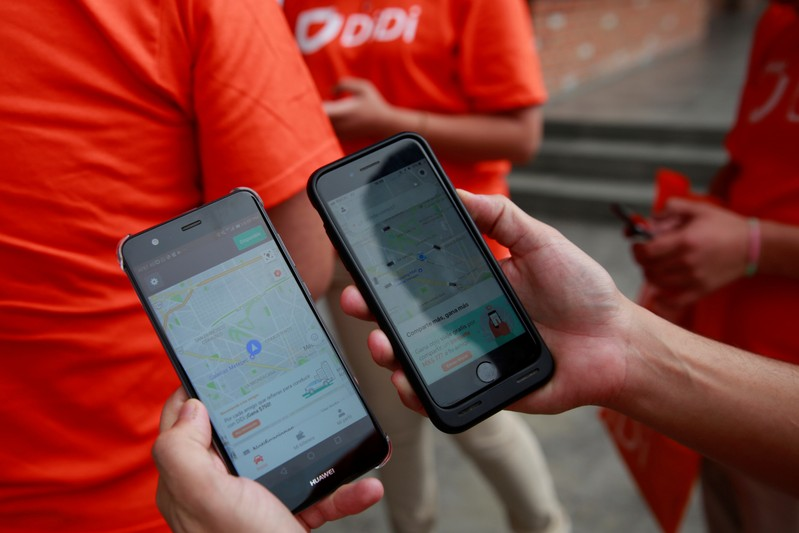 FILE PHOTO:  An employee shows the app of China's Didi Chuxing as they launches their ride service in Toluca,