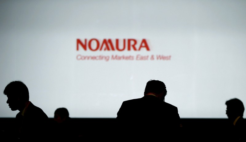 FILE PHOTO: Investors stand in front of a screen showing the logo of Nomura Holdings in Tokyo