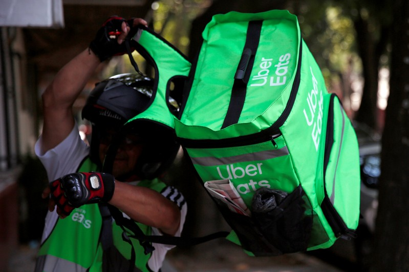 FILE PHOTO: A man puts on a delivery bag with the logo of Uber Eats in Mexico City