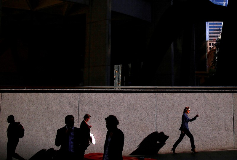 A woman carries a shopping bag as she walks with other pedestrians along a street on a spring day in the central business district of Sydney