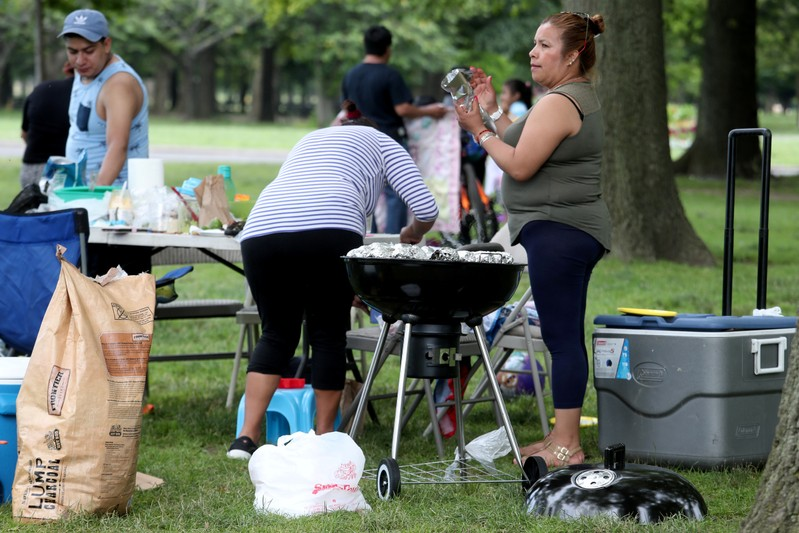 FILE PHOTO: Woman puts corn on the grill at Flushing Meadows Park in the Queens borough of New York City