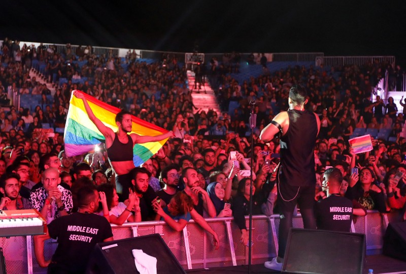 FILE PHOTO: A fan of Lebanese alternative rock band Mashrou' Leila holds a rainbow flag during their concert at the Ehdeniyat International Festival in Ehden town