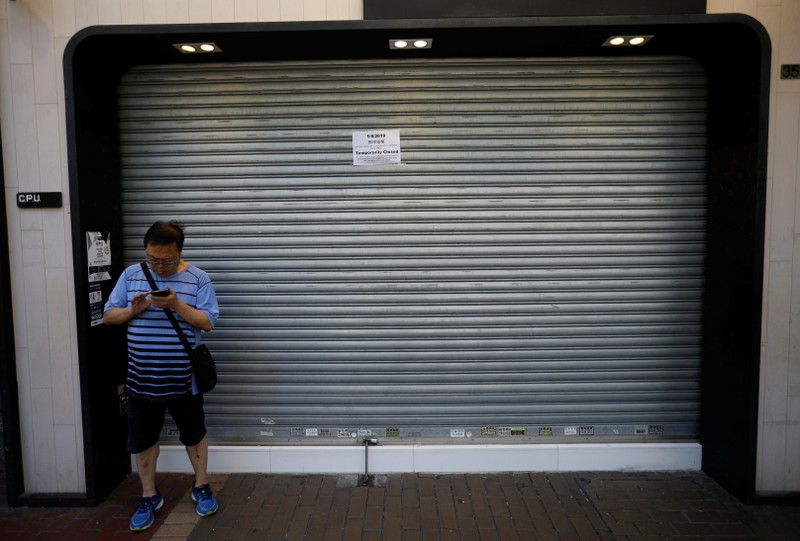 A man stands in front of a shop, with a notice on its shutters announcing it is closed for the day due to traffic disruptions, during a general strike in Hong Kong