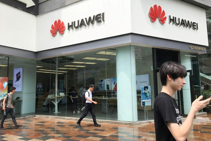 People walk past a Huawei store in Shenzhen