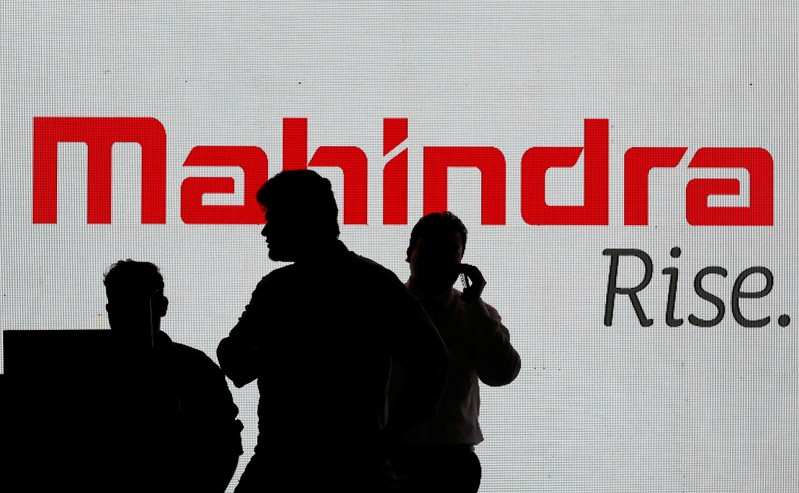 People walk past a screen displaying Mahindra and Mahindra logo before the start of a news conference in Mumbai