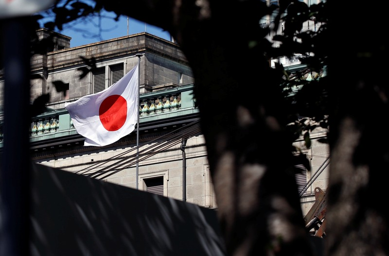 A Japanese flag flutters atop the Bank of Japan building under construction in Tokyo