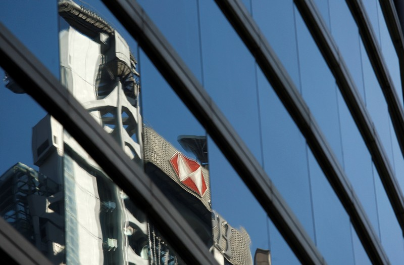 FILE PHOTO: The HSBC headquarters is reflected on the facade of a commercial building in Hong Kong