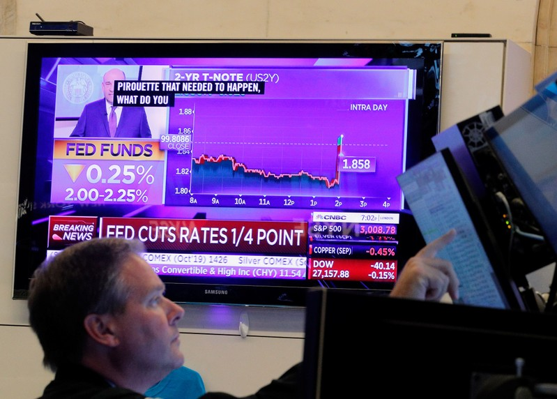 FILE PHOTO: A trader looks on as a screen displays the U.S. Federal Reserve interest rates announcement on the floor of the New York Stock Exchange (NYSE) in New York