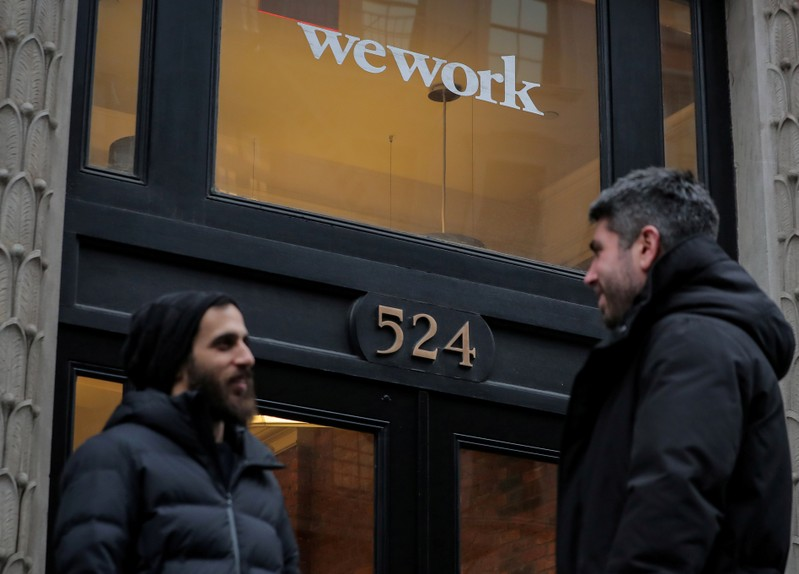 FILE PHOTO: People stand outside a WeWork co-working space in New York
