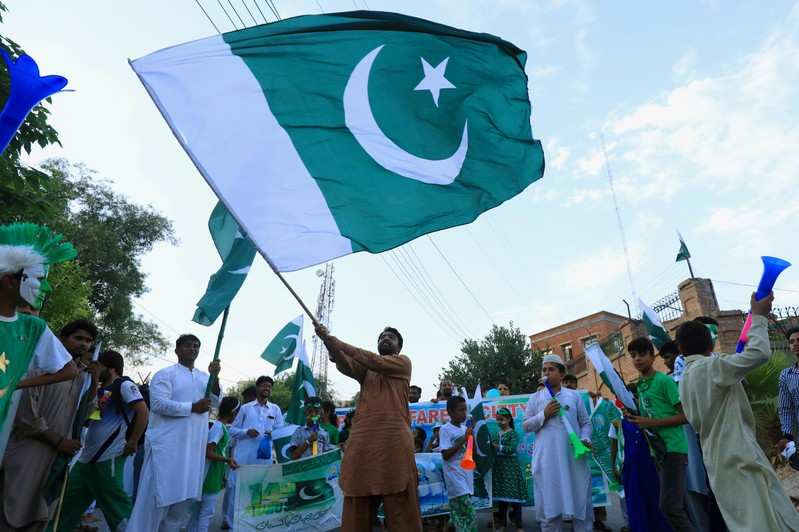 A man from the Pakistan's Hindu community waves national flag with others, during a rally to express solidarity with the people of Kashmir on Pakistan's 72nd Independence Day in Peshawar