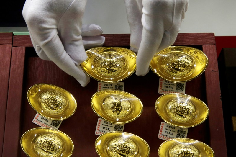 FILE PHOTO: A sales assistant places gold ornaments at Caibai Jewelry store in Beijing
