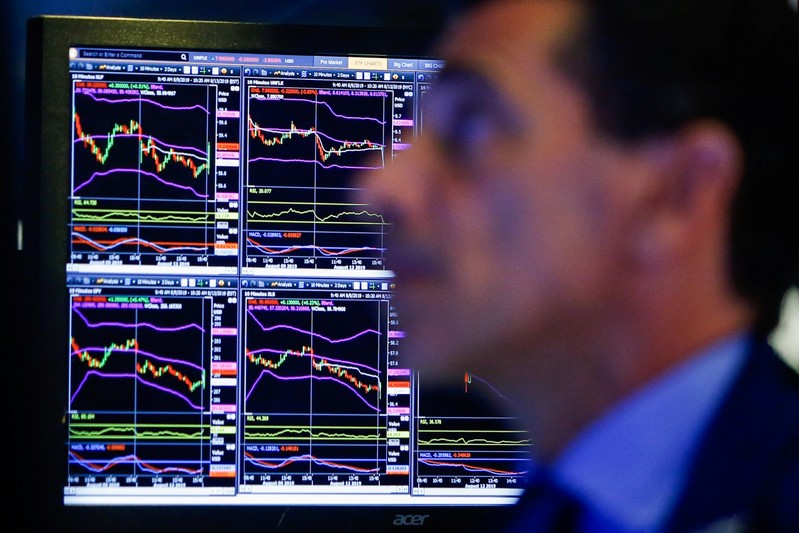 A trader looks at screens as he works on the floor at the New York Stock Exchange (NYSE) in New York