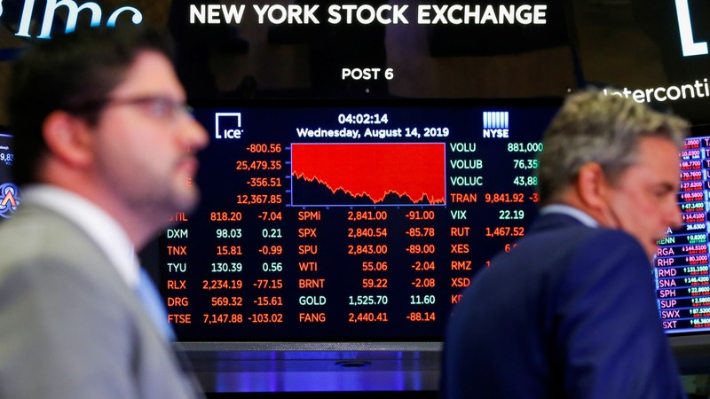A screen shows the numbers after the closing bell as traders work on the NYSE floor in New York