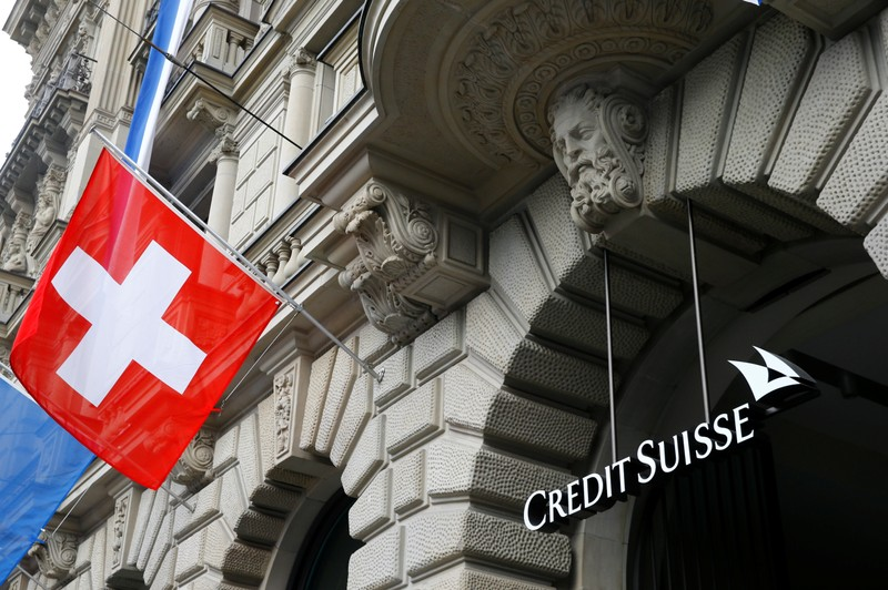 Switzerland's national flag flies beside a logo of Swiss bank Credit Suisse in Zurich