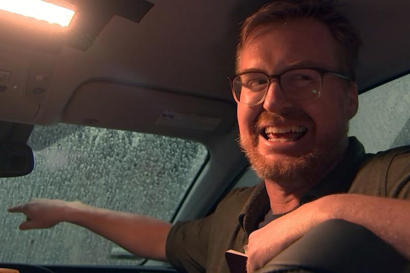 Comedian Kurt Braunohler laughs as he tells a joke in a car during a