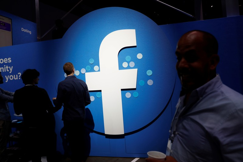 FILE PHOTO - Attendees walk past a Facebook logo during Facebook Inc's F8 developers conference in San Jose