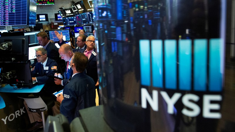 FILE PHOTO: Traders work on the floor at the New York Stock Exchange (NYSE) in New York