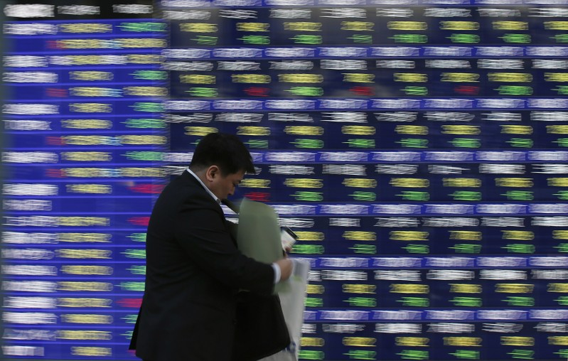 FILE PHOTO: A man walks past a stock quotation board outside a brokerage in Tokyo